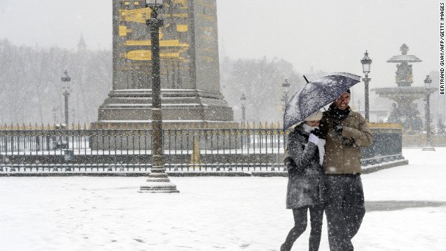 A couple walk on a snowy sidewalk at Place de la Concorde in Paris on Tuesday, March 12, during a heavy snowstorm. Twenty-six regions in northwest and northern France were put on orange alert because of heavy snowfall.
