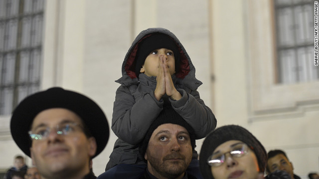 A boy sits on his father's shoulders in St. Peter's Square.
