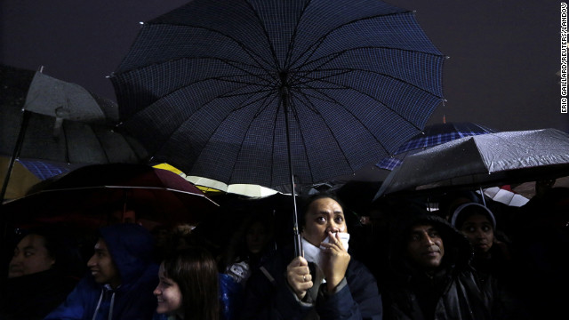 People under umbrellas react to the news while waiting for the new pope to appear.