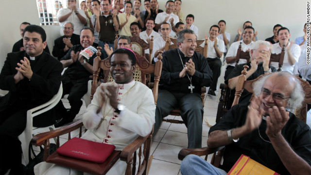 Fortunatus Nwachukwu, in white, the Vatican's ambassador to Nicaragua, applauds as he watches a local television station announcing the new pope with others in Managua, Nicaragua.