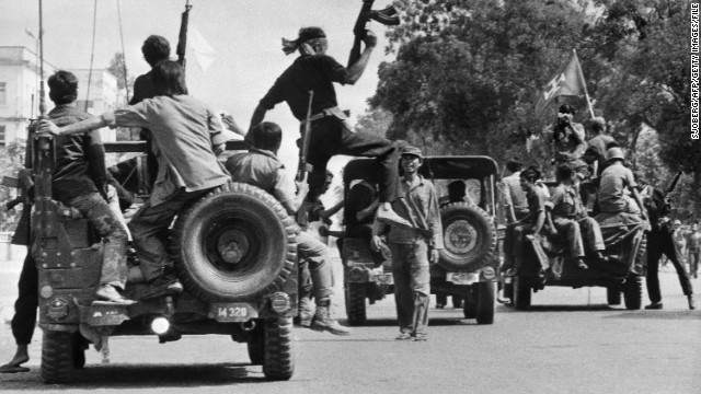 Khmer Rouge guerilla soldiers wearing black uniforms drive atop jeeps through a street of Phnom Penh on the day Cambodia fell under their control in April 1975. 