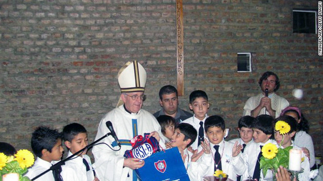 Bergoglio poses with school children and the emblem of Argentina's San Lorenzo football team. 