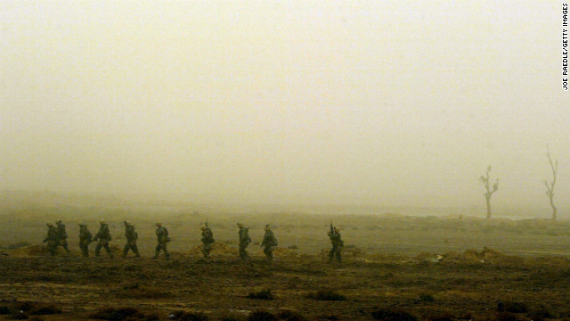 Marines walk single-file through the desolate landscape in Nasiriyah on March 26, 2003. As night falls on the city, the troops are on alert for a counterattack.