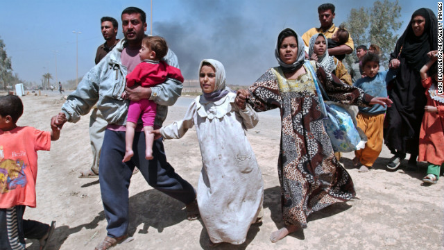 Iraqis flee Baghdad on April 11, 2003, as the capital city descended into chaos with widespread looting and lawlessness.