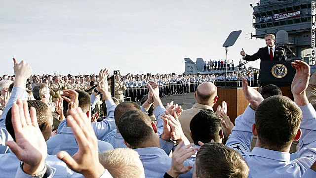 Sailors applaud as President Bush addresses the nation aboard the USS Abraham Lincoln on May 1, 2003. Standing beneath a banner that read