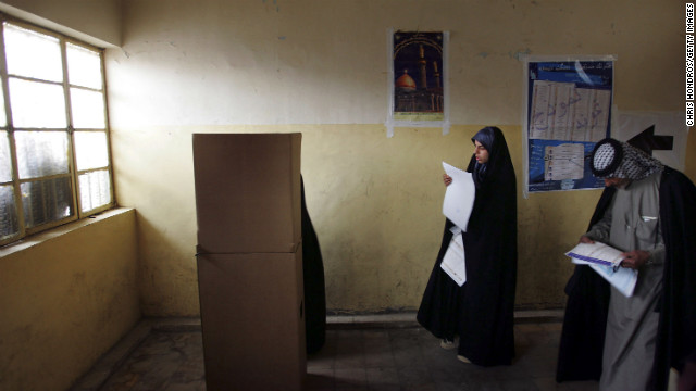 Iraqis look over their ballots on election day in the Sadr City neighborhood of Baghdad on January 30, 2005. It was the country's first multiparty election in half a century.