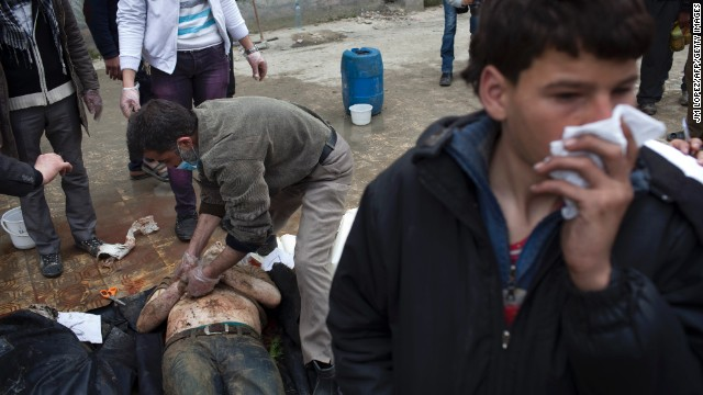 Syrian men search for their relatives amongst the bodies of civilians executed and dumped in the Quweiq River on March 11.