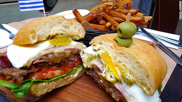 The Uruguayan chivito piles skirt steak or filet mignon with layers of ham and bacon, accompanied by onion, mayonnaise, lettuce, tomato, mozzarella, olives, hard-boiled egg and lettuce. Pictured: chivito from Tabar in Brooklyn.