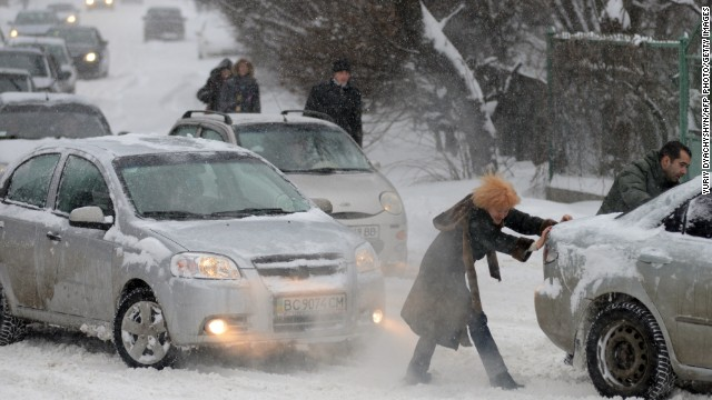 People push a stuck car as heavy snow falls in Lviv, Ukraine, on Friday, March 15.