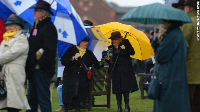 Spectators watch the action during a rain-lashed last day of the Cheltenham horse racing festival in Gloucestershire, England, on March 15.