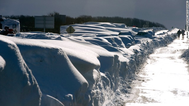 People walk by cars covered in snow around Beaumont-Hague, northern France, following a heavy snowstorm, on Wednesday, March 13.