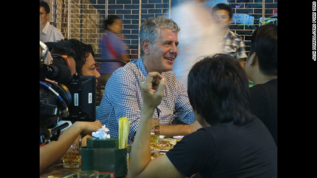 Bourdain sits down with a band, Side Effect, at a barbecue restaurant, Kaung Myat, in Yangon.