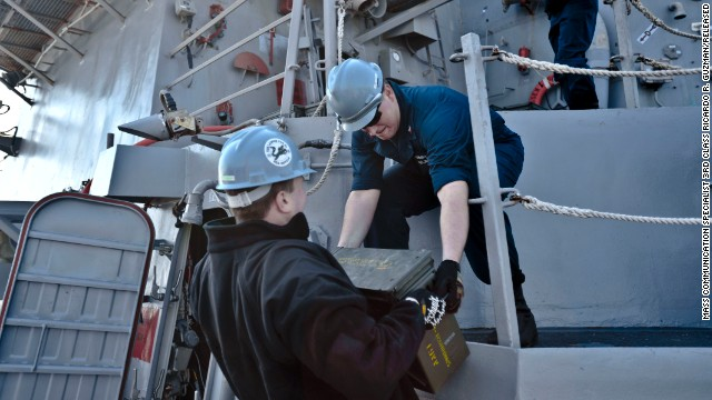 Fire Controlman 2nd Class Jason Titcombe, left, hands Fire Controlman 2nd Class Joshua Clements ordnance aboard destroyer USS Lassen, in this Navy handout photo taken on March 5.