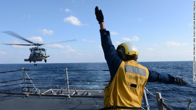 U.S. Navy Boatswain's Mate 3rd Class Brittany Chiles signals to an SH-60B Seahawk helicopter as it lands on the flight deck of destroyer USS McCampbell on March 4 in the Pacific Ocean, in this Navy handout photo.