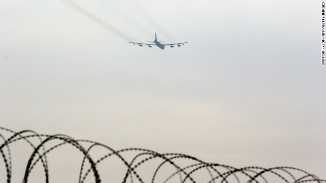 A B-52 bomber flies over the barbed-wire fence of a U.S. air base in Osan, South Korea, on Tuesday, March 19.