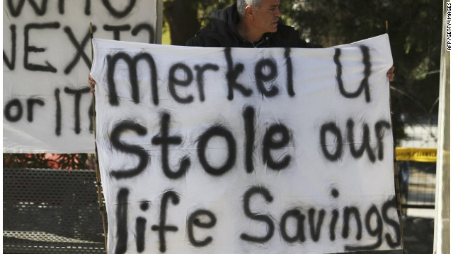 A Cypriot man holds a banner against the EU bailout deal and German Chancellor Angela Merkel.