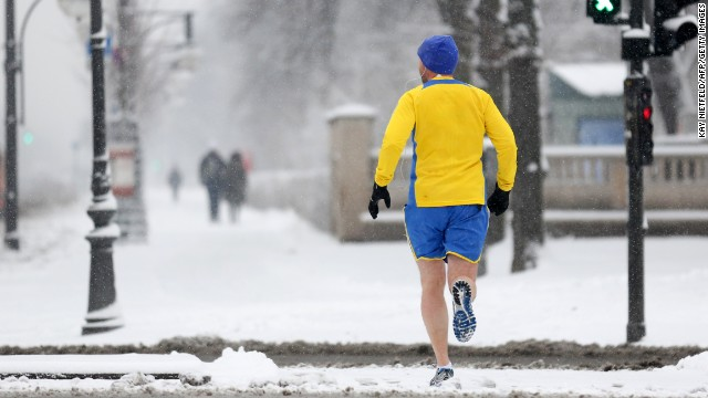A jogger runs across a snow-covered street in Berlin on March 19.