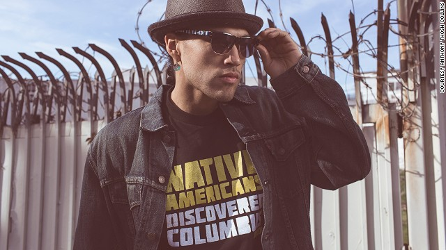 "Fashion blog Beyond Buckskin released a lookbook in March 2013 intended to ""highlight the professionalism of Native American artists and designers"" and encourage investment in ""Native-made fashion and art as forms of economic development in Indian Country."" In this image from the lookbook, model Martin Sensmeier wears a ""Native Americans Discovered Columbus Tee"" by Navajo Jared Yazzie for OxDx, Blueberry Copper Earrings by Nicholas Galanin (Tlingit/Aleut), and beaded sunglasses by Candace Halcro (Cree/Metis)."