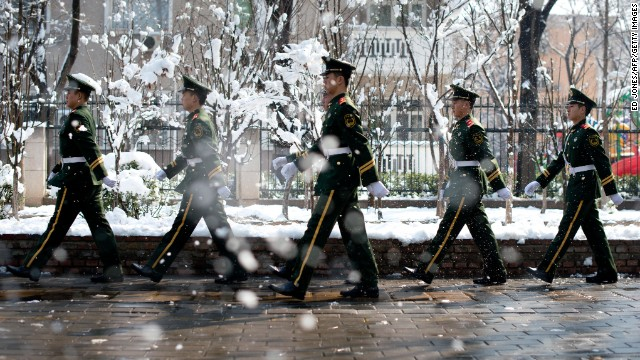 Paramilitary guards walk along a street following an overnight snowfall in Beijing on March 20.