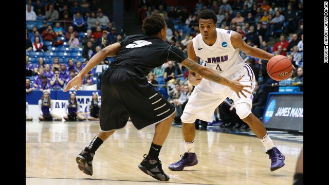 Charles Cooke of the James Madison Dukes drives against C.J. Garner of LIU Brooklyn during the first half on March 20.