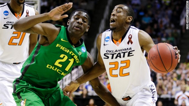 Markel Brown of Oklahoma State drives against Damyean Dotson of Oregon on March 21.