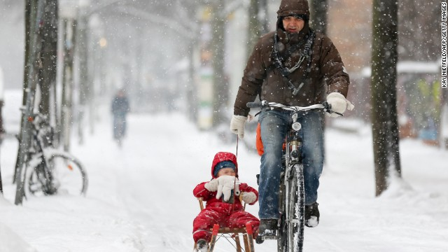 A bicyclist pulls a child on a sled through the snow on Thursday, March 21, in Berlin.