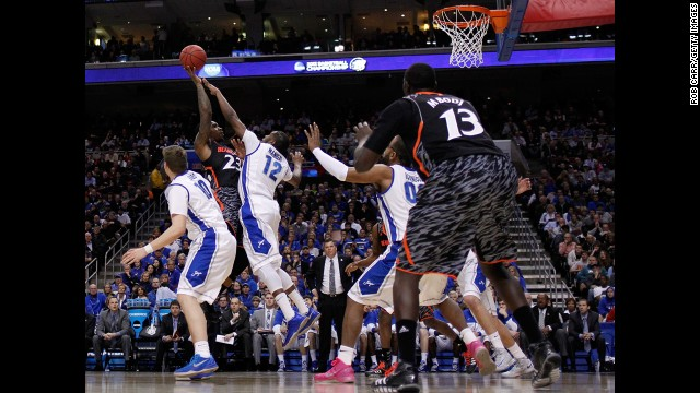 Sean Kilpatrick of the Cincinnati Bearcats, second from left, shoots over Jahenns Manigat of the Creighton Bluejays on March 22.