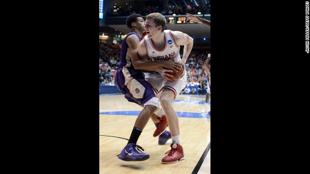 Cody Zeller of the Indiana Hoosiers, right, handles the ball against Charles Cooke of the James Madison Dukes on March 22.