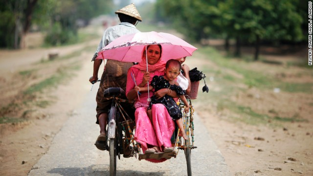 People ride in a rickshaw on a road north of the town of Sittwe.