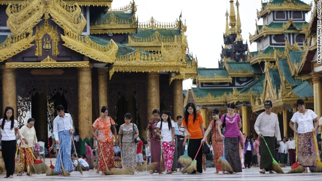 Volunteers sweep the floors at the golden Shwedagon Pagoda in Yangon.