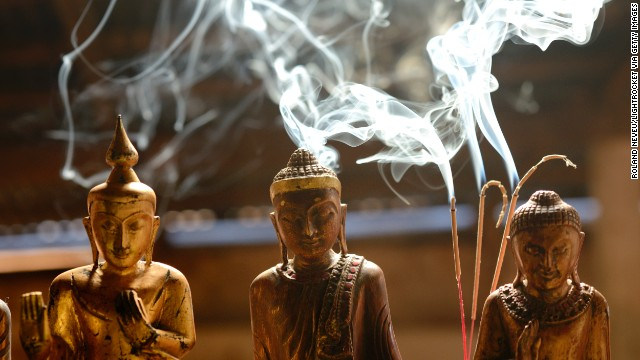 Wooden figures sit for sale as incense burns behind them at a stall in Indein, a village by Inle Lake.