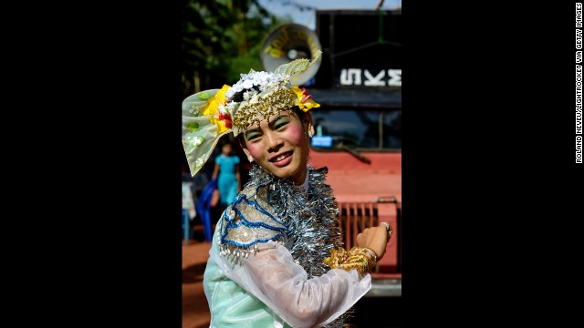 A young Burmese man dressed as a woman entertains residents of a neighborhood in Mawlamyine.