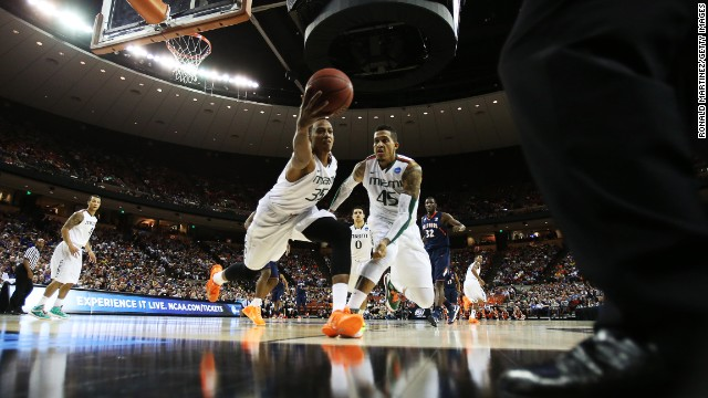 Kenny Kadji of the Miami Hurricanes tries to save a loose ball while teammate Julian Gamble looks on in the first half against the Illinois Fighting Illini on March 24 in Austin, Texas. Miami won 63-59.