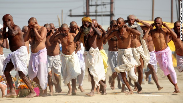 Bihari Hindu priests run while holding their ears during a ritual at the Sangam on March 6.