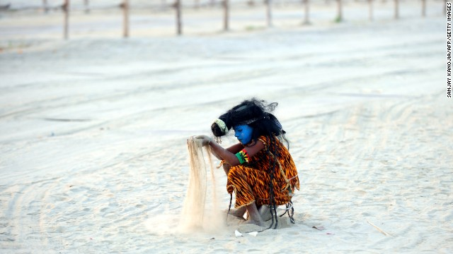 An Indian child dressed as the Hindu god Shiva plays with sand on the banks of the Sangam in Allahabad on March 5.