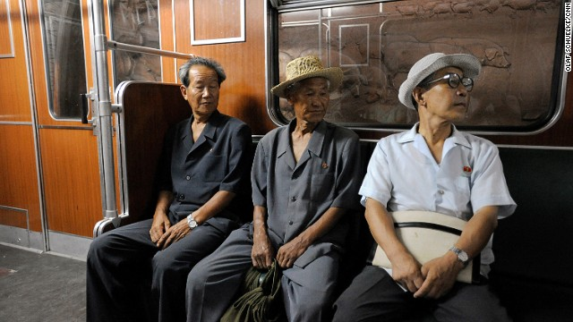 Three North Koreans ride a metro train in Pyongyang. The carriages were purchased from Germany in 1998. Not visible in this image, inside of each carriage hang small pictures of deceased leaders, neatly framed behind glass.