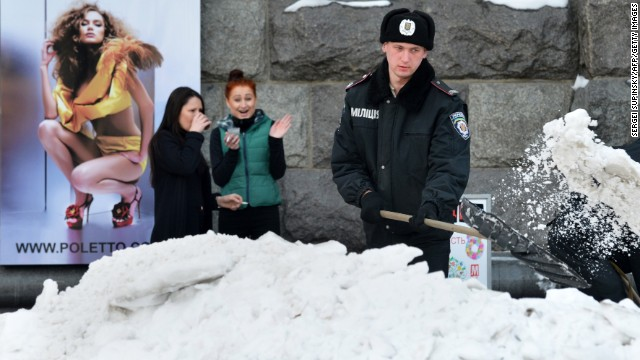 Young women watch a policeman clear snow and ice from a road in Kiev, Ukraine, on Tuesday, March 26.