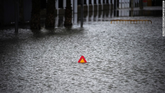 A road sign peeks above a flooded street in Badolatosa, Spain, on Monday, March 25.