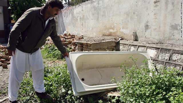 Contractor Yusufzai looks at a bathtub left over from the demolition on May 1, 2012.