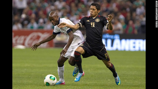 Javier Aquino of Mexico fights for the ball with DaMarcus Beasley of the U.S.