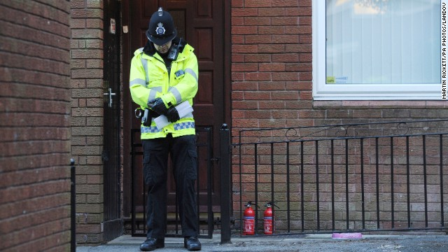 A police officer stands outside the front door of a house Atherton, England, where the body of a 14-year old girl, thought to be Jade Anderson, was found mauled by 'aggressive and out of control' dogs.