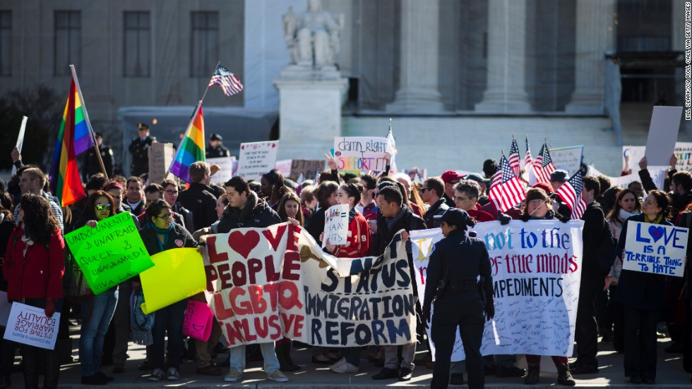Supporters of same-sex marriage wave flags and signs as they rally in front of the U.S. Supreme Court on Wednesday, March 27, in Washington. The justices heard two cases this week related to state and federal laws restricting same-sex marriage.