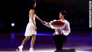 China\'s Olympic silver medal figure skater Tong Jian, right, proposes to his girlfriend and skating partner Pang Qing at the end of a skating exhibition in Shanghai in 2011.
