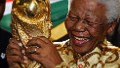 South African former President Nelson Mandela holds the Jules Rimet World cup, 15 May 2004 at the FIFA headquarters in Zurich.