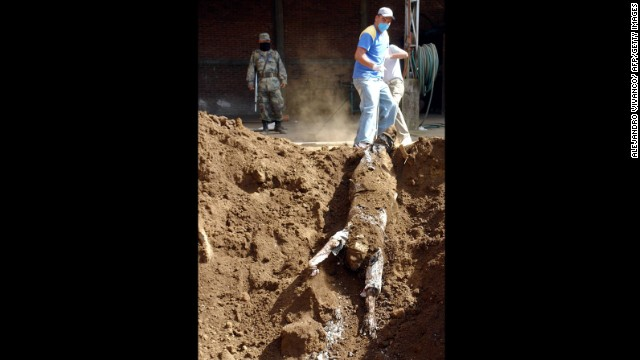 Workers unearth the bodies of three unidentified people whose killings are believed to be related to drug trafficking, according to the state police department, in Uruapan on Janurary 4, 2007.