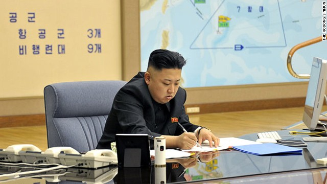 Kim Jong Un works during a briefing in this undated photo.