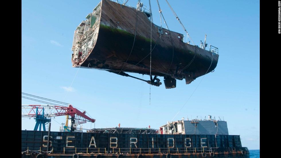 The stern of the USS Guardian, the last piece of grounded ship, is removed by a crane vessel on Saturday, March 30. The U.S. Navy minesweeper became trapped on a reef off the western Philippine island of Palawan on January 17. The Navy has pledged to clean up debris and restore the reef as much as possible.