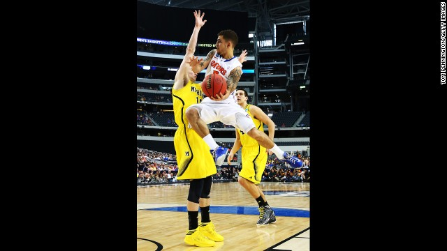Scottie Wilbekin of Florida goes up against Nik Stauskas, left, of Michigan.