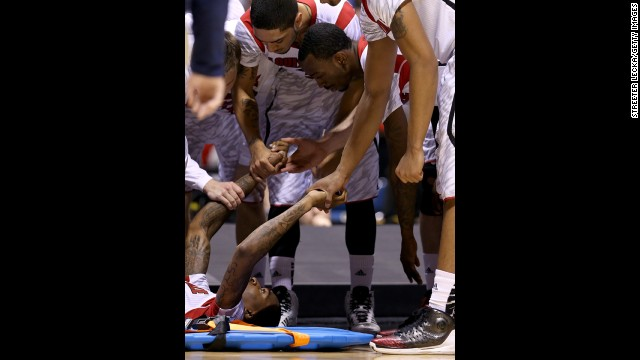 Kevin Ware, bottom left, is comforted by his teammates as his leg is examined by medical staff.