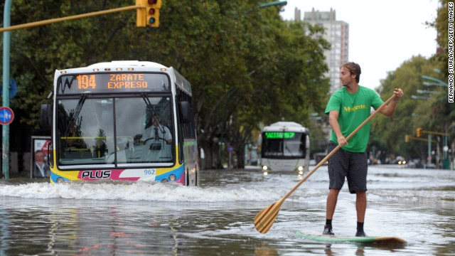 A man paddle boards through the flooded streets of Argentina's capital Tuesday, April 2, 2013.